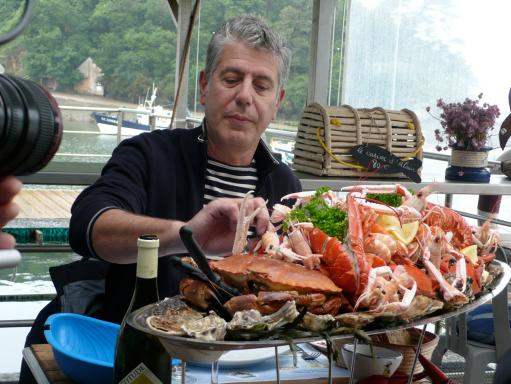 Anthony Bourdain sampling a food platter on his travels. (Photo Source: The Travel Channel)