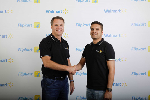 """Doug McMillon, Walmart President and CEO, and Binny Bansal, Flipkart Co-Founder and Group CEO, shaking hands. On Twitter, Bansal wrote """"Delighted to welcome @Walmart as our long-term partners in @Flipkart. This is the dawn of a new era for India's #StartUp ecosystem."""""""