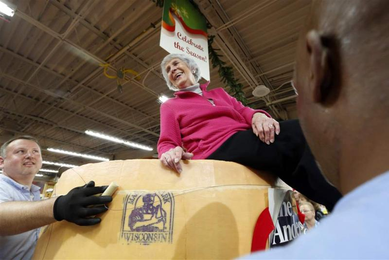 Fran Anderson sits on top of holiday cheddar cheese; Photo Source: www.toledoblade.com/