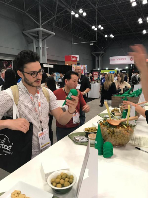 Food professionals exploring the 'Have an Olive Day' stand at the Summer Fancy Food Show