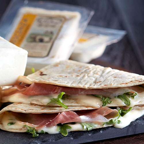 BelGioioso Crescenza Stracchino wrapped in a piadina with baby arugula and Prosciutto di Parma