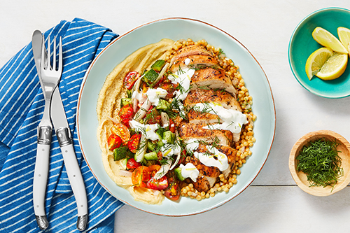 The Chicken Gyro Couscous Bowl features a zaatar spiced chicken cutlet on a bed of hummus and couscous topped with fresh tomatoes and cucumbers drizzled with a creamy feta sauce
