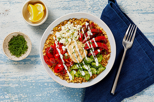 The Mediterranean Hummus & Couscous Bowl features smoked paprika hummus beneath spiced, roasted red peppers and grape tomatoes, paired with a marinated cucumber salad in a creamy lemon dressing